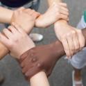 5 Hände internationaler Herkunft halten sich gegenseitig