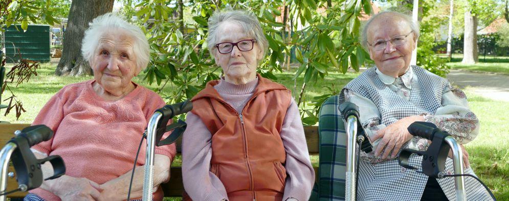 3 Bewohnerinnen sitzen im Garten des Altenpflegeheims Naunhof auf einer Bank