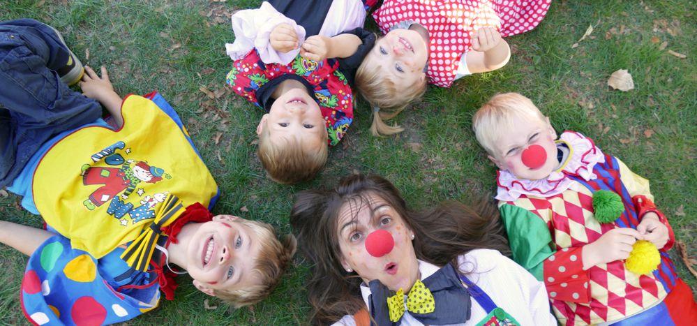 Kinder und Erzieherin liegen als Clowns verkleidet auf der Wiese