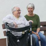 Betreuerin mit alter Dame auf der Bank