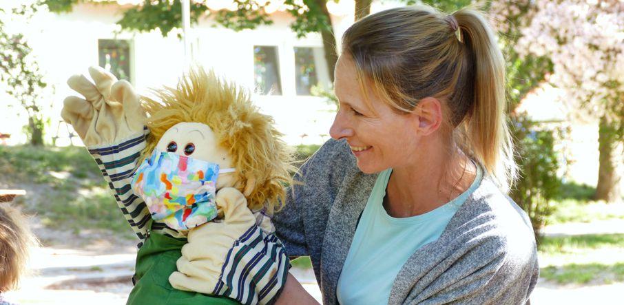 Erzieherin demonstriert Corona-Regeln für Kinder mit Handpuppe, die Mundschutz trägt