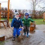 Zwei Jungen hüpfen mit viel Spaß in einer Pfütze