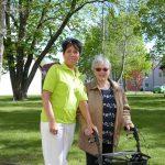 Pflegerin und alte Dame bei Spaziergang im Garten