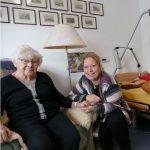 Lächelnde alte Dame mit Heimleiterin in Bewohnerzimmer
