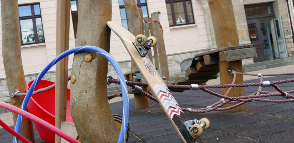 Skateboard, Reifen und andere Spielgeräte vor dem Hort der Grundschule Pegau