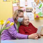 Heimbewohnerin und Betreuerin lesen Grußkarte