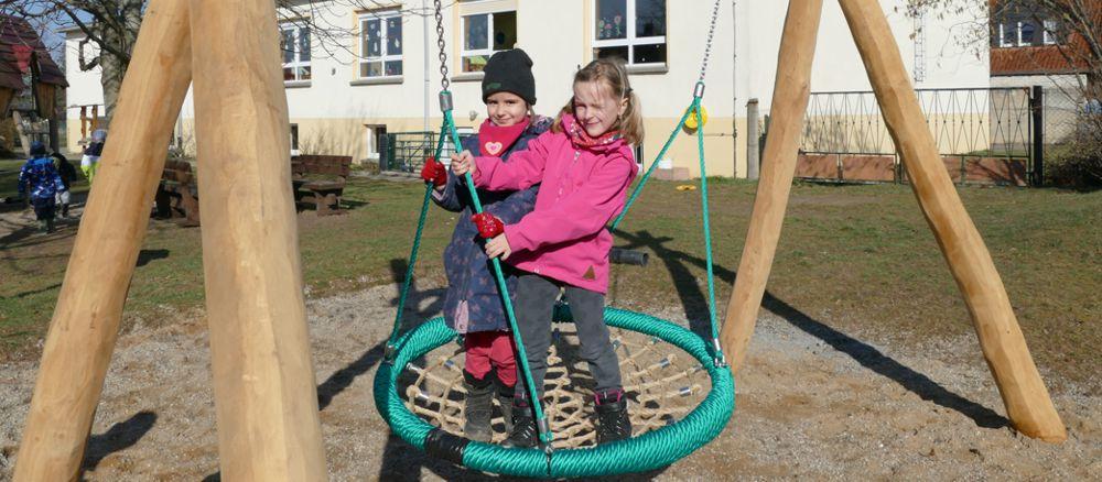 2 Mädchen auf neuer Schaukel, die dank Spenden für Kindergarten angeschafft werden konnte