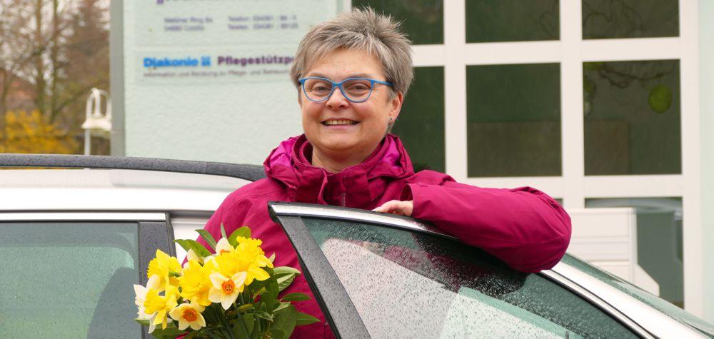 Hospizhelferin am Auto mit Narzissenstrauß